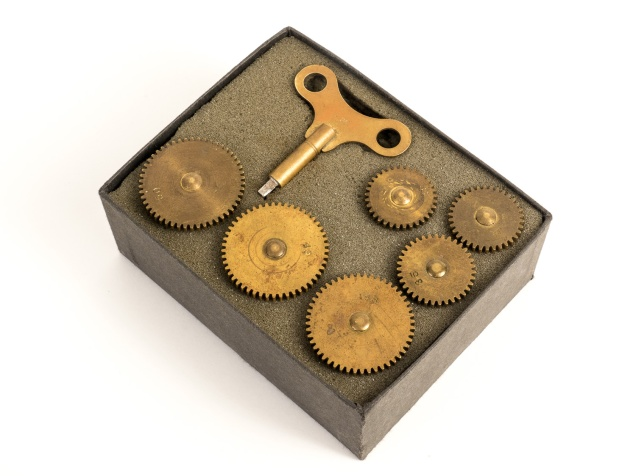 Set of brass gears and the key used to wind the Cirkut's clockwork motor.